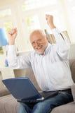Vieil homme heureux s'asseyant sur le sofa avec l'ordinateur portatif Photographie stock