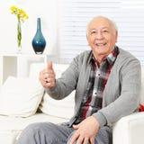 Vieil homme heureux tenant des pouces  Photographie stock