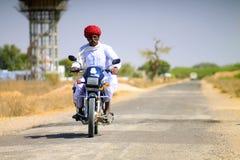 Vieil homme indou sur une motocyclette Photographie stock libre de droits