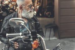 Vieil homme intéressé sur la moto Photo stock