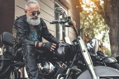 Vieil homme intéressé vérifiant la motocyclette Photo stock