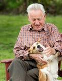 Vieil homme jouant avec le chien Photographie stock libre de droits