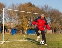 Vieil homme jouant le football Photographie stock