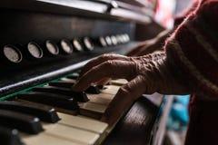 Vieil homme jouant le piano dans une fin vers le haut de vue de son Han froissé Photos stock