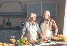 Vieil homme joyeux et femme préparant le dîner dans la cuisine images stock