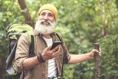 Vieil homme joyeux trimardant dans la région boisée avec le navigateur de smartphone Image libre de droits