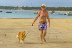Vieil homme marchant en avant avec son chien à la plage Images libres de droits