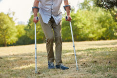 Vieil homme marchant sur des béquilles Photo stock