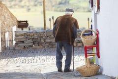 Vieil homme marchant sur la rue d'un village Images libres de droits