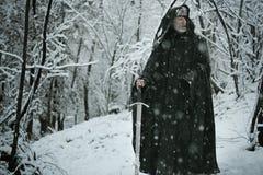 Vieil homme mystérieux dans la forêt de neige Photographie stock libre de droits