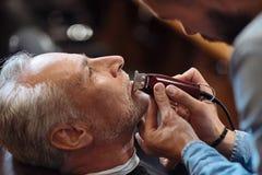 Vieil homme obtenant sa barbe rasée par le coiffeur Image libre de droits