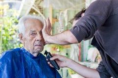 Vieil homme obtenant sa barbe rasée par le jeune homme qualifié à la maison photos libres de droits