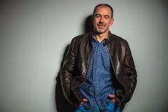 Vieil homme occasionnel de sourire dans la veste en cuir avec des mains dans des poches Image stock