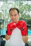 Vieil homme portant les gants de boxe rouges s'exerçant dans la forme physique ou le gymnase Images stock