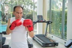 Vieil homme portant les gants de boxe rouges s'exerçant dans la forme physique ou le gymnase Photos stock