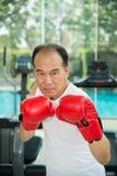 Vieil homme portant les gants de boxe rouges s'exerçant dans la forme physique ou le gymnase, concept de santé Photo stock