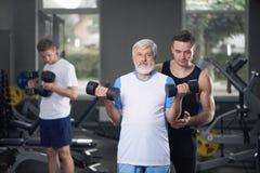 Vieil homme posant avec des haltères, formation d'entraîneur image libre de droits