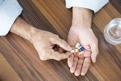 Vieil homme prenant des pilules Photo stock