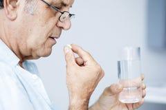 Vieil homme prenant des pilules Images libres de droits