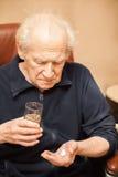 Vieil homme prenant des pilules Photographie stock libre de droits