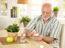 Vieil homme prenant la pillule à la maison Photos libres de droits