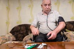 Vieil homme réfléchi avec l'appareillage de tension artérielle Photo stock