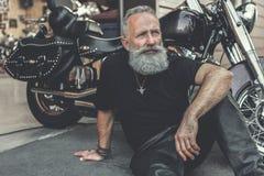 Vieil homme rêveur plaçant près de la moto Images stock