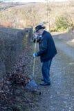 Vieil homme ratissant les feuilles tombées dans le jardin, jardinage d'homme supérieur images libres de droits
