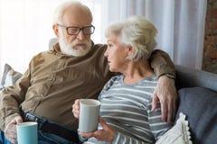Vieil homme regardant sérieusement la dame mûre tout en parlant Photo libre de droits