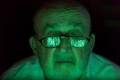 Vieil homme regardant un écran d'ordinateur entaillé photo libre de droits