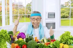Vieil homme renonçant à des pouces à la maison Images stock
