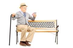 Vieil homme sénile avec la canne, sur le banc imaginant jouant des cartes avec Images stock