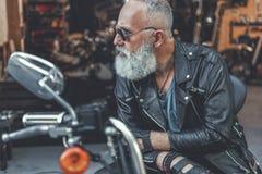 Vieil homme sévère prêt pour l'usage de la motocyclette Image stock
