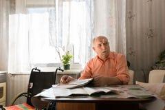 Vieil homme s'asseyant à son Tableau avec le journal Photos stock