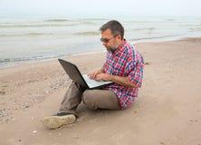 Vieil homme s'asseyant avec un ordinateur portable Images stock