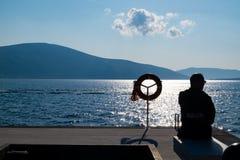 Vieil homme s'asseyant dans le dock image stock