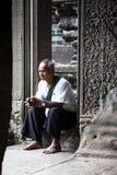 Vieil homme s'asseyant dans un temple en pierre images libres de droits