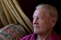 Vieil homme s'asseyant par l'hublot dans la maison photo stock