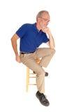 Vieil homme s'asseyant sur la pensée de chaise Images libres de droits