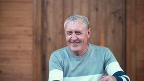 Vieil homme s'asseyant sur le porche de la maison Grand-père faisant le visage drôle et petite-fille courant à lui, étreintes 4K Photos stock