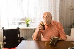 Vieil homme s'asseyant tenant le jet de bouteille de la lotion après-rasage Photos stock