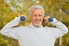 Vieil homme s'exerçant avec des haltères Image libre de droits