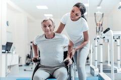 Vieil homme satisfait s'asseyant dans un fauteuil roulant Images libres de droits