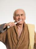 Vieil homme se brossant les dents images stock