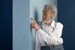 Vieil homme se penchant sur un mur Photos libres de droits