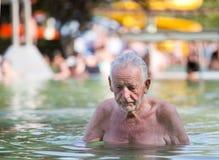 Vieil homme se reposant dans la piscine Image libre de droits