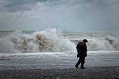 Vieil homme seul marchant le long de la côte, vue arrière images stock
