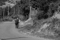 Vieil homme seul marchant le long de la route images libres de droits