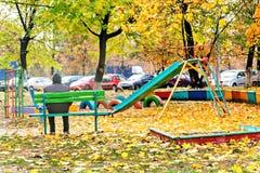 Vieil homme seul s'asseyant sur le terrain de jeu pendant l'automne Photographie stock libre de droits