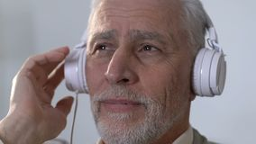 Vieil homme songeur dans des écouteurs écoutant la musique, se rappelant la jeunesse, nostalgie clips vidéos